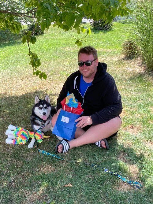 Kris Wilson in the shade with his dog Aspen